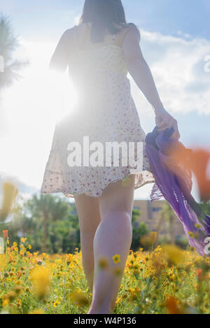 Woman walking through a field of flowers carrying a scarf - Stock Photo