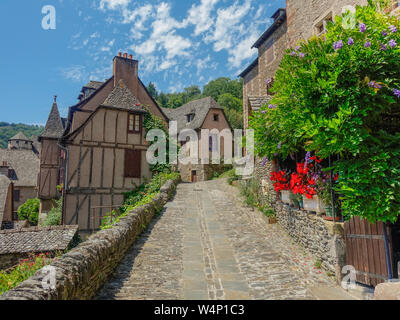 Conques, Midi Pyrenees, France - July 31, 2017: Typical narrow stone streets in the village of Conques - Stock Photo