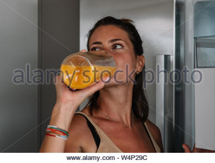 Caucasian woman opens the fridge of her kitchen and drinks a freshly squeezed orange juice - Stock Photo