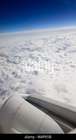 Aerial view from aircraft window with clouds - Stock Photo