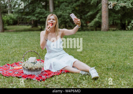 beautiful young women sitting on the plaid, eating watermelon, making selfie. Nature, picnic. Copyspace - Stock Photo