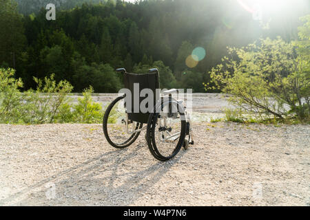 Empty wheelchair parked in park, health care concept - Stock Photo