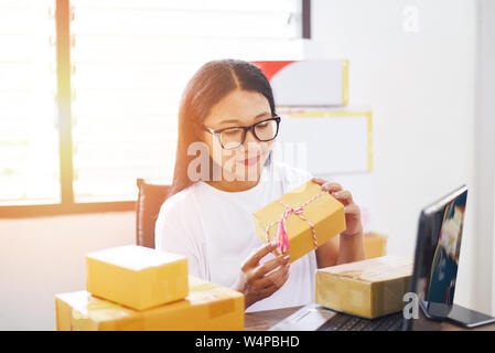 selling online ecommerce shipping online shopping delivery and order startup small business owner working / asian young woman packing cardboard box pa - Stock Photo
