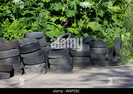 old car tires stacked near the forest. concept of ecological disaster and illegal dumps. - Stock Photo
