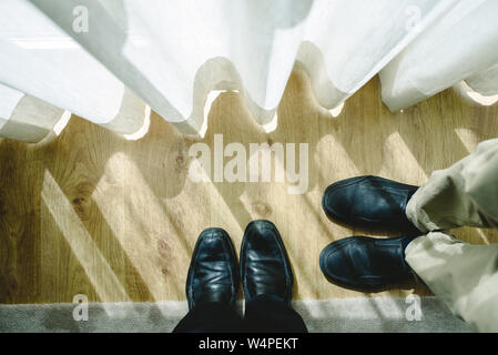 Two pairs of feet with their black shoes facing, viewed from above. - Stock Photo