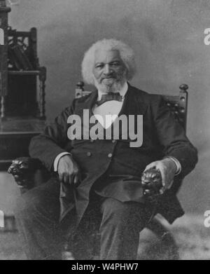 Black and white portrait photograph of African-American abolitionist, writer, orator, statesman, and social reformer, Frederick Douglass, depicted seated, in three-quarter length view, wearing a dark, double-breasted suit with a bow tie, facing the camera, with white hair and beard, and a serious expression on his face, 1880. From the New York Public Library. () - Stock Photo