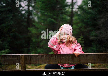 Adorable little girl in pink jacket sitting behind wooden fence and adjusting beanie on background with blurred dark forest near Reykjavik - Stock Photo