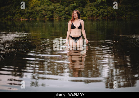 Front view of young woman standing in lake - Stock Photo
