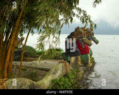 two dragons statues beside lake beratan, bali - Stock Photo