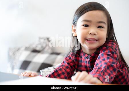 Asian Cute little girl sitting smiling - Stock Photo