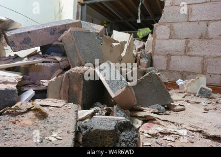Demolished breeze block interior wall inside a factory. Part of a reconstruction project.  Building site rubble - Stock Photo
