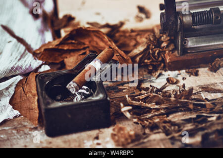 close up of a Cuban cigar and a black ceramic ashtray on the wooden table whit dried and cured tobacco leaves. - Stock Photo