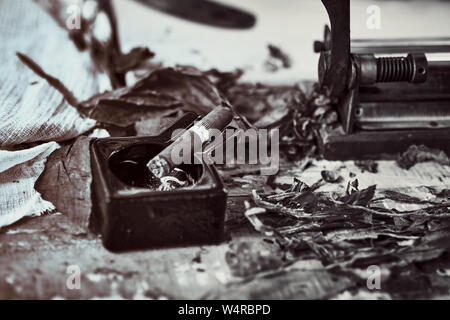close up of a Cuban cigar and a black ceramic ashtray on the wooden table whit dried and cured tobacco leaves. bw image - Stock Photo