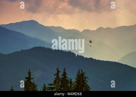 Moody picture of evening mountain ridges, Austrian alps, with a small paraglider on a horizon. - Stock Photo