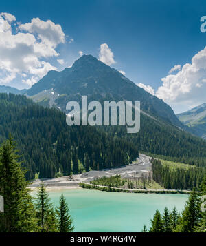 excavators and wheel loaders at the mouth of a mountain river in Arosa in the Swiss Alps move silt and rock sediment for construction use - Stock Photo