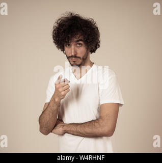 Studio shot of cheerful young millennial male with bear and great hair smiling and making funny and friendly gestures. Isolated on neutral background. - Stock Photo