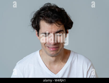 Portrait of young sad man crying in emotional pain looking desperate and distressed. Millennial male suffering from depression. In mental health and s - Stock Photo
