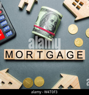 Wooden houses, a calculator, keys, coins and blocks with the word Mortgage. Buying a home in debt. Purchase a house on credit. Loan on the property. I