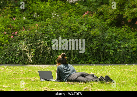 CARDIFF, WALES - JULY 2019: Student lying on grass in a public park in Cardiff looking at a laptop computer. - Stock Photo