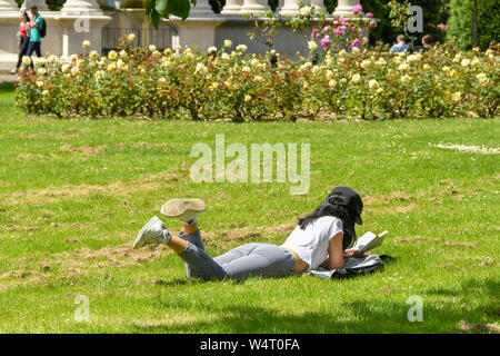 CARDIFF, WALES - JULY 2019: Student lying on grass in a public park in Cardiff reading a book . - Stock Photo
