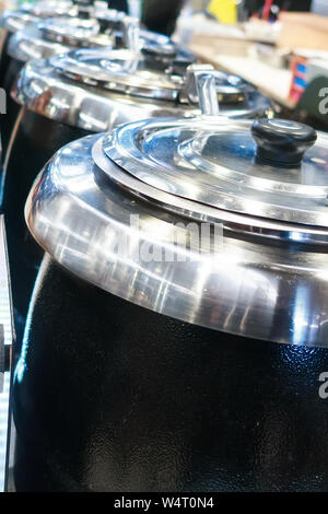 Large steel professional pots in a row in restaurant kitchen at the market food court - Stock Photo
