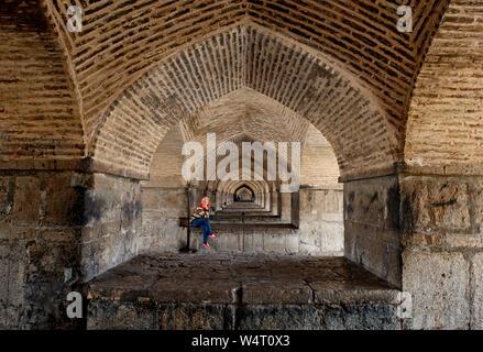 Woman sitting inside The Khaju Bridge, Isfahan, Iran - Stock Photo