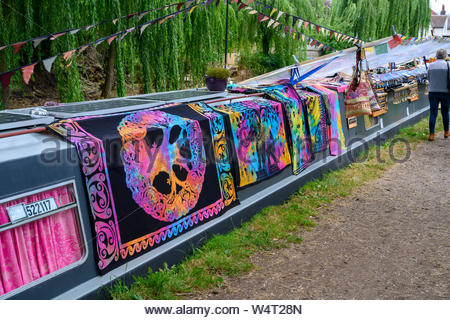 Brightly coloured fabrics draped over a moored narrowboat decorated with bunting on the Shropshire Union Canal in Gnosall - Stock Photo