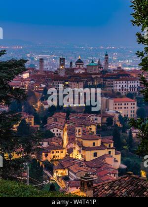 Bergamo, Italy, 21/11-18. View over Città Alta of Bergamo from the hill of Castello di San Vigilio after sunset. Corridoni in the distance. - Stock Photo