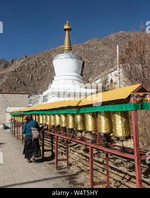 China, Tibet, Lhasa, A worshipper spins prayer wheels in front of a stupa at the Drepung Buddhist Monastery  which  founded in 1416 AD and was the largest monastery in all of Tibet  housing up to 10 000 monks at one time. - Stock Photo