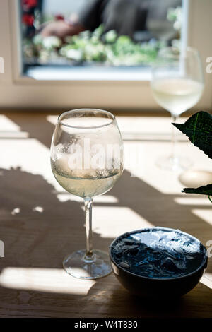 Two glasses of white wine and a blue spirulina smoothie bowl - Stock Photo