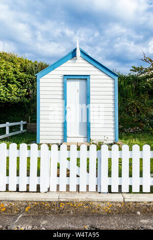 A traditional blue and white wooden beach hut behind a white picket fence on the seafront at Westward Ho!, Devon, UK - Stock Photo