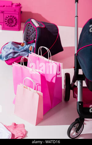 baby carriage with doll, pink shopping bags and baby stroller - Stock Photo