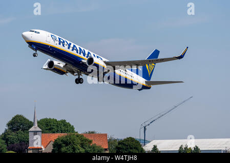 Ryanair Boeing 737 jet airliner plane EI-GJP taking off from London Southend Airport, Essex, UK above building construction work, crane and church - Stock Photo