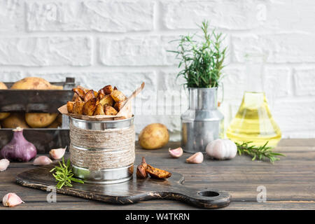 Baked young potatoes in a rustic style with sour cream - Stock Photo