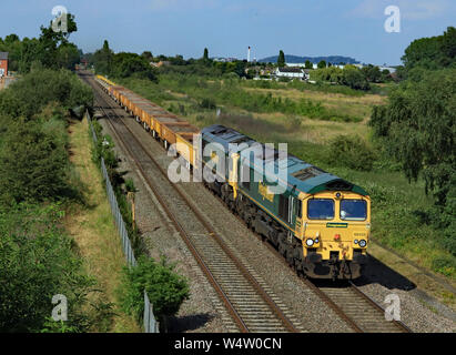 Freightliner diesel locomotives 66555 and 66617 travelling from Burton on Trent towards Tamworth with a freight train pass Branston in Staffordshire. - Stock Photo
