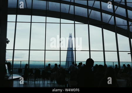 The Shard skyscraper in grey and blue colours in London, UK shot from the Sky Garden restaurant. In the foreground of the photo is a crowd of people. - Stock Photo