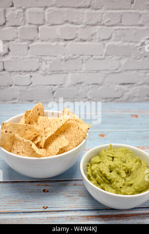 view of a bowl with spicy guacamole next to a bowl of nachos on a blue wooden table - Stock Photo
