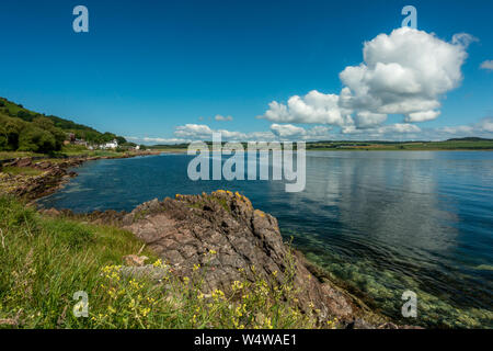 Clear water and blue skies on a beautiful sunny day on the coast at Kilchattan Bay, Isle of Bute, Scotland - Stock Photo