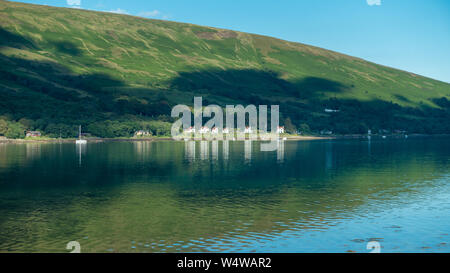 The stunning coastline around the Kyles of Bute, image of Colintraive houses with reflections taken from Rhubodach, Isle of Bute - Stock Photo