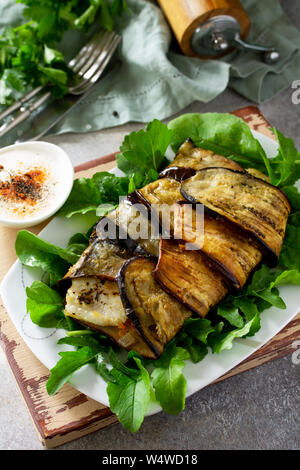 Delicious fish baked with vegetables in an eggplant grilled on a stone or slate table. - Stock Photo