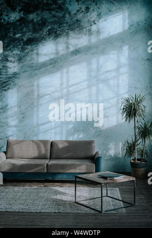 The interior of a simple loft-style living room with blue walls, a textile sofa, a coffee table and a tropical palm tree - Stock Photo