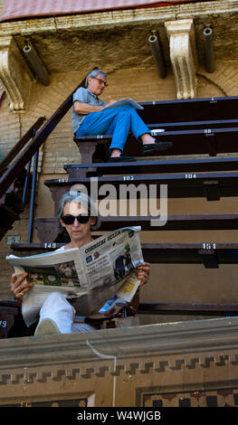 Man and woman each read newspapers while awaiting the start of the Palio in the Piazza di Campo in Siena, Italy - Stock Photo