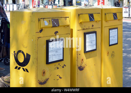 Heidelberg, Germany - June 2019: Three yellow official public mail boxes in a bad state on street - Stock Photo