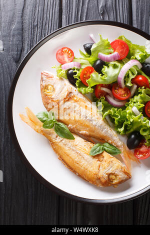 Tasty fried pink dorado or gilt-head bream fish with vegetable salad close-up on a plate on the table. Vertical top view from above - Stock Photo