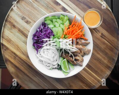 An overhead shot of a dish with chicken meat, carrot, cucumbers, red cabbage, and white noodles with lemon in a round white bowl near a sauce - Stock Photo