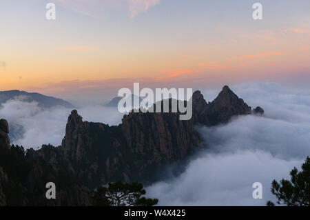 Sunset on the Aiguilles of Bavella surrounded by a sea of clouds during the GR20 hike in Corsica, France - Stock Photo