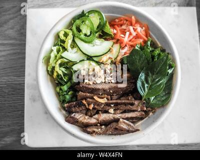 An overhead shot of cooked meat with sliced vegetables in a white round bowl - Stock Photo