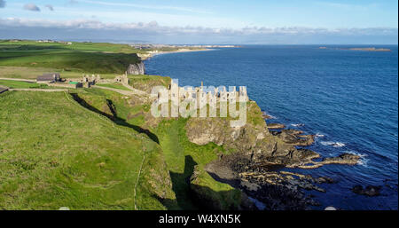 Ruins of medieval Dunluce Castle on a steep cliff near Bushmills. Northern coast of County Antrim, Northern Ireland, UK. Aerial view in sunrise light. - Stock Photo
