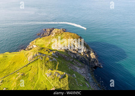 Torr Head headland, rocky cliff and peninsula in County Antrim, Northern Ireland, near Ballycastle. Aerial photo with a motorboat - Stock Photo
