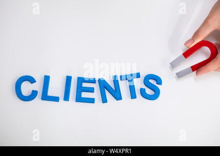 Businessperson Attracting Blue Clients Text With Horseshoe Magnet Over White Background - Stock Photo